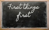 Expression - First things first - written on a school blackboar — Stock Photo
