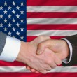 Businessmen handshake after good deal in front of america flag - Stock Photo