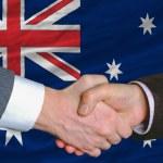 Businessmen handshake after good deal in front of australia flag — Stock Photo