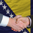 Businessmen handshake after good deal in front of bosnia herzegovina flag — Stock Photo #7995313