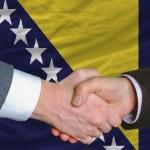 Businessmen handshake after good deal in front of bosnia herzegovina flag — Stock Photo