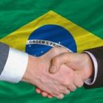 Businessmen handshake after good deal in front of brazil flag — Stock Photo