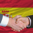 Businessmen handshake after good deal in front of spain flag — Stock Photo
