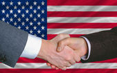 Businessmen handshake after good deal in front of america flag — Stock Photo