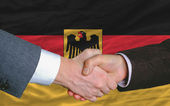 Businessmen handshake after good deal in front of germany flag — Stock Photo