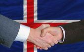 Apretón de manos de los empresarios después de buen trato frente a la bandera de islandia — Foto de Stock