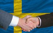 Businessmen handshake after good deal in front of sweden flag — Stock Photo