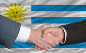 Businessmen handshake after good deal in front of uruguay flag — Stock Photo