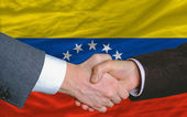 Businessmen handshake after good deal in front of venezuela flag — Stock Photo