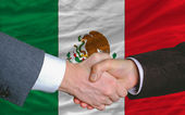 Businessmen handshake after good deal in front of mexico flag — Stock Photo