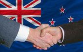 Businessmen handshake after good deal in front of new zealand fl — Stock Photo