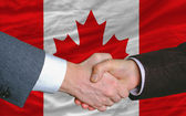 Businessmen handshake after good deal in front of canada flag — Stock Photo