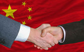 Businessmen handshakeafter good deal in front of china flag — Stock Photo
