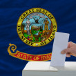 Man voting on elections in front of flag US state flag of idaho — Stock Photo