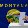 Man voting on elections in front of flag US state flag of montan — Stock Photo