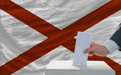 Man voting on elections in front of flag US state flag of alabam — Stock Photo