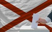 Muž hlasování o volbách před vlajkou nás státní vlajka alabam — Stock fotografie