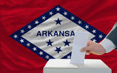 Man voting on elections in front of flag US state flag of arkans — Stockfoto