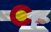 Man voting on elections in front of flag US state flag of colora — ストック写真