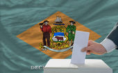 Man voting on elections in front of flag US state flag of delawa — ストック写真