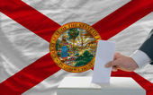 Man voting on elections in front of flag US state flag of florid — Stockfoto