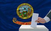 Man voting on elections in front of flag US state flag of idaho — Stockfoto
