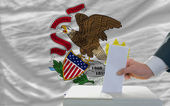 Man voting on elections in front of flag US state flag of illino — ストック写真