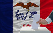Man voting on elections in front of flag US state flag of iowa — Стоковое фото