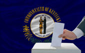 Man voting on elections in front of flag US state flag of kentuc — Foto de Stock