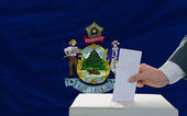 Man voting on elections in front of flag US state flag of maine — Stock Photo