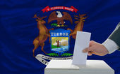 Man voting on elections in front of flag US state flag of michig — Stockfoto
