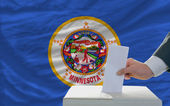Man voting on elections in front of flag US state flag of minnes — Foto Stock