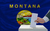 Man voting on elections in front of flag US state flag of montan — Foto de Stock