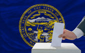 Man voting on elections in front of flag US state flag of nebras — Stockfoto