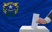 Muž hlasování o volbách před vlajkou nás státní vlajka nevada — Stock fotografie