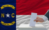 Man voting on elections in front of flag US state flag of north — Stock Photo