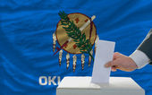 Man voting on elections in front of flag US state flag of oklaho — Stock Photo