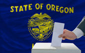 Man voting on elections in front of flag US state flag of oregon — Foto de Stock