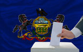 Man voting on elections in front of flag US state flag of pennsy — ストック写真
