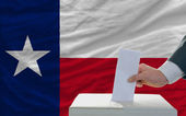 Man voting on elections in front of flag US state flag of texas — Zdjęcie stockowe