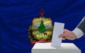 Muž hlasování o volbách před vlajkou nás státní vlajka vermon — Stock fotografie