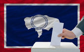 Man voting on elections in front of flag US state flag of wyomin — Stock Photo