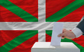 Man voting on elections in front of national flag of basque — Stockfoto
