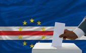 Man voting on elections in front of national flag of capeverde — Stockfoto