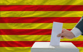 Man voting on elections in front of national flag of catalonia — Stock fotografie