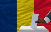 Man voting on elections in front of national flag of chad — Стоковое фото