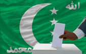 Man voting on elections in front of national flag of comoros — Стоковое фото