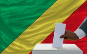 Man voting on elections in front of national flag of congo — Photo