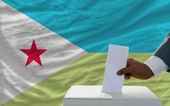 Man voting on elections in front of national flag of djibuti — Stock Photo