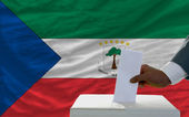 Man voting on elections in front of national flag of equatorial — ストック写真